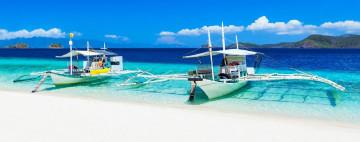 Philippinen Urlaub: weißer Sandstrand und traditionelle Boote
