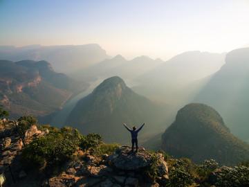 Mann mit ausgestreckten Armen vor den Bergen Südafrikas -Copyright South Africa